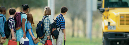 Image of students waiting for approaching school bus at bus stop